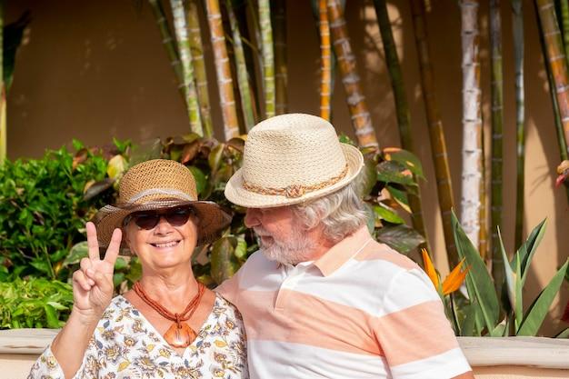 열대 정원에서 여름 휴가를 즐기는 사랑에 빠진 행복한 은퇴한 커플