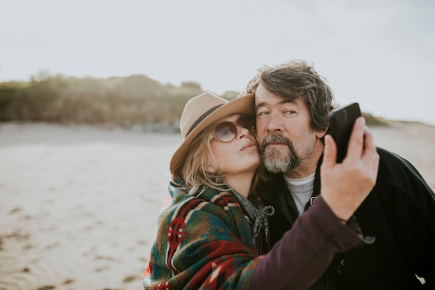 Happy retired couple take a selfie by the beach