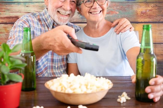 맥주와 팝콘 두 병 술집에 앉아 축구 경기를보고 행복 한 은퇴 한 커플. 두 매력적인 수석 사람