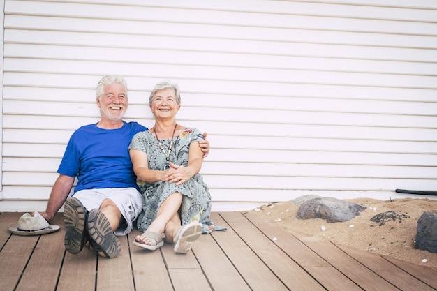 Счастливая пенсионная концепция образа жизни с пожилыми старшими мужчиной и женщиной, сидящими на деревянной земле и улыбающимися вместе со счастьем и радостью. веселые зрелые люди наслаждаются совместной жизнью в объятиях и любви