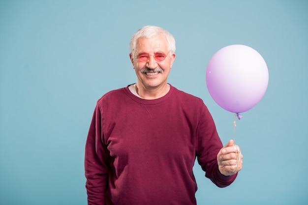 Счастливый пенсионер в пуловере и очках держит воздушный шар