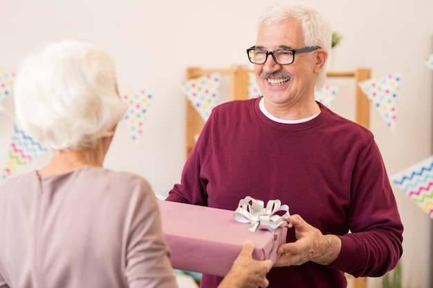 Happy retired man taking giftbox with present given by his wife during home celebration