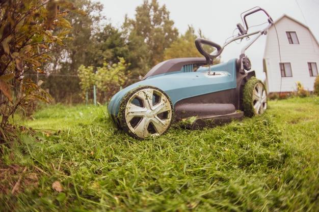 행복한 은퇴한 노인은 잔디 깎는 기계로 정원에서 잔디를 깎습니다. 정원 작업입니다.