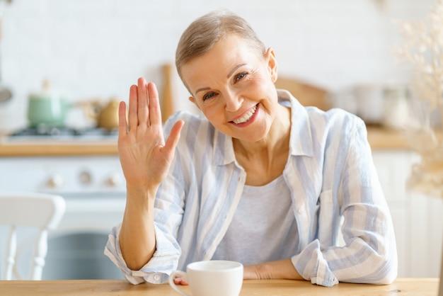 Счастливая пенсионерка машет рукой, здороваясь во время видеозвонка дома