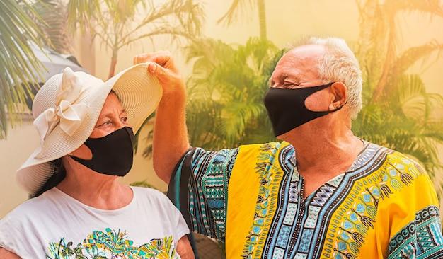 安全のためにマスクを着用して幸せな退職者。引退した老人が老婦人の帽子の下を覗き、妻を見ます。