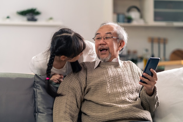 Happy retirement elderly man sitting on sofa at living room with granddaughter using digital tablet together.