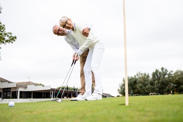 Счастливый пенсионный период и пожилые люди, наслаждающиеся игрой в гольф.