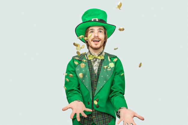 黄金のコインを広げて笑っている聖パトリックのスーツを着た幸せな金持ちの若い男。彼らは飛ぶ。男が見上げる。グレーに分離。