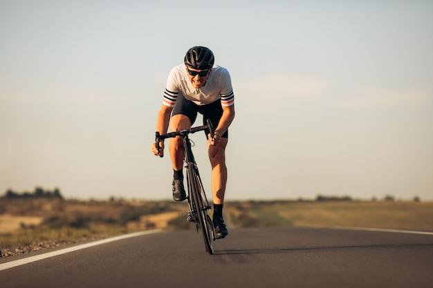 신선한 공기에 아침 자전거를 즐기는 보호용 헬멧과 미러 안경의 행복한 도로 사이클