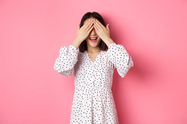 驚きを待っている幸せなロマンチックなアジアの女の子、目を閉じて、ピンクの背景の上に立って、驚いて、何かを期待して笑っています。