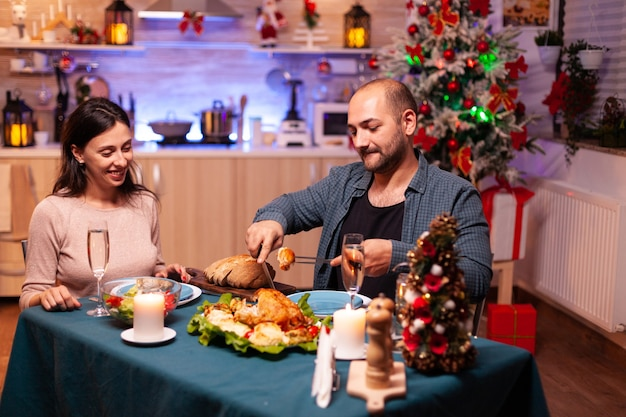 Happy romantic couple eating christmas dinner sitting at dinning table