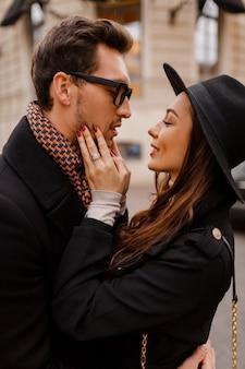 ヨーロッパでの新婚旅行で一緒に旅行している間、幸せなロマンチックなカップルが顔を合わせて、通りでいちゃつくと抱き合っています。