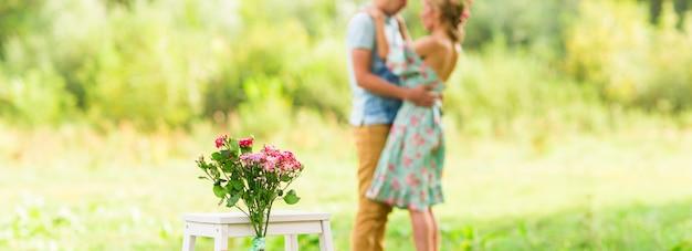 幸せなロマンチックなカップルの抱擁。花に焦点を当てます。セレクティブフォーカス。