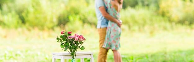 幸せなロマンチックなカップルの抱擁。花に焦点を当てます。セレクティブフォーカス。 Premium写真