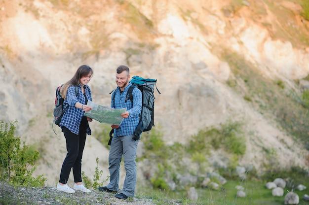 登山の手を繋いでいるバックパックで幸せなロマンチックなカップル男と女の旅行者