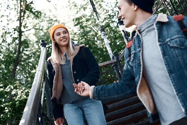 観光客の幸せなロマンチックなカップルが降りて、階段に手をつないでいます