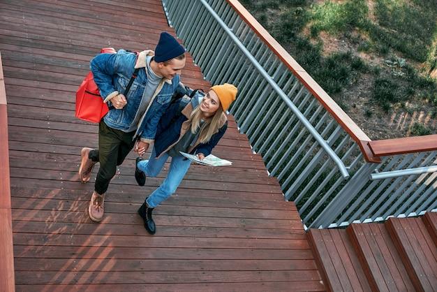 観光客の幸せなロマンチックなカップルは、階段の上面図に手をつないでいます