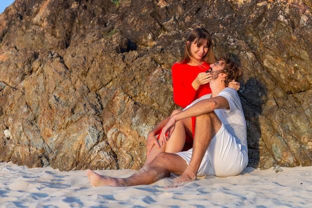 Счастливая романтическая пара на тропическом пляже на закате.