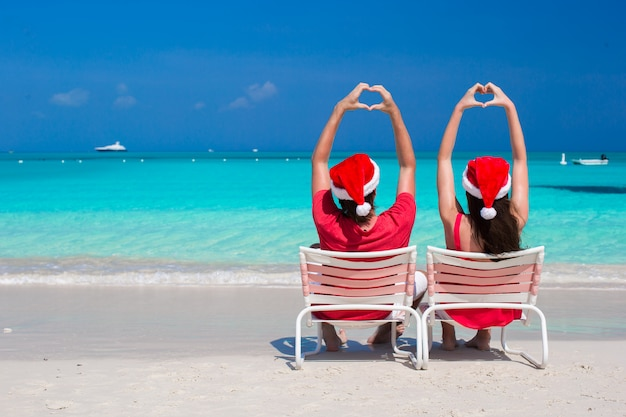 Happy romantic couple in red santa hats at beach making hearts