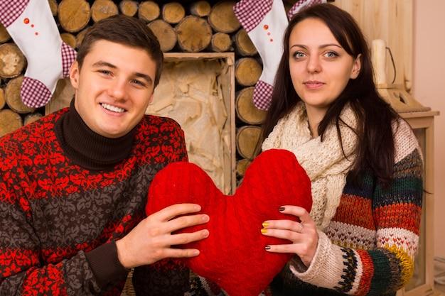 カメラに微笑んで伝統的なクリスマスのストッキングで飾られた素朴な木製の囲炉裏の前に座って赤いハートのクリスマスの装飾と幸せなロマンチックなカップル