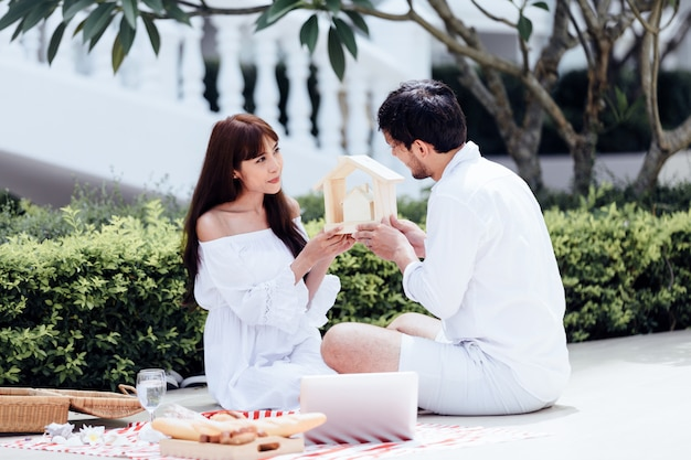 Happy romantic couples lover talking and drinking wine while having a picnic at home