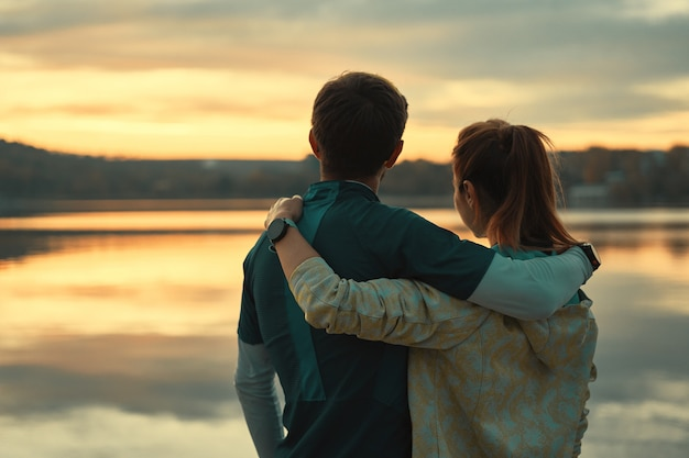 Happy romantic fit young couple enjoying sunset