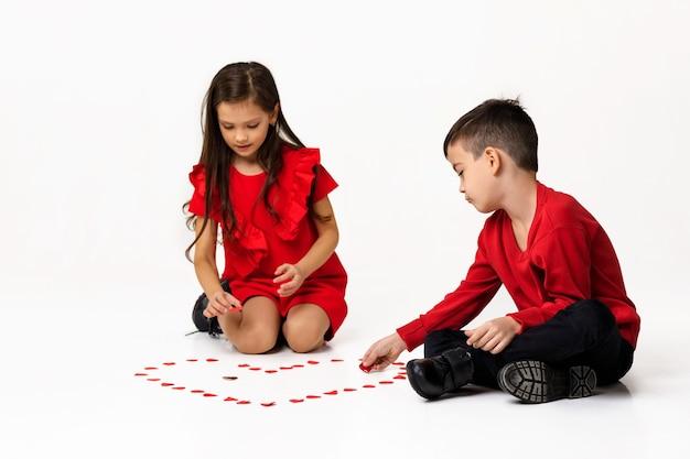 Счастливая романтическая маленькая пара, девочка и мальчик, делают большую форму сердца из маленьких бумажных сердечек на полу