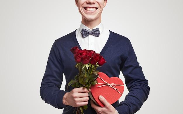 Счастливый романтический мужчина в элегантном наряде с галстуком-бабочкой держит букет красных роз и подарочную коробку в форме сердца для празднования дня святого валентина