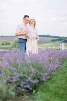 보라색 꽃 라벤더 밭을 걷고, 서서 포옹하는 사랑에 빠진 행복한 낭만적인 성숙한 커플