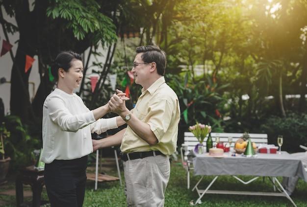 Happy romantic senior couple dancing at home garden
