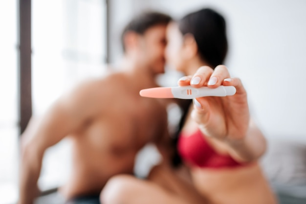 Happy romantic young couple sit on bed and kiss. woman show pregnancy test with two strips. camera concentrated on that.