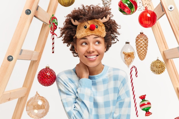 Happy romantic young woman with curly hair waits for merry christmas enjoys cozy domestic atmosphere wears reindeer sleepmask and pajama uses ladder to hang toys on fir tree. winter time concept