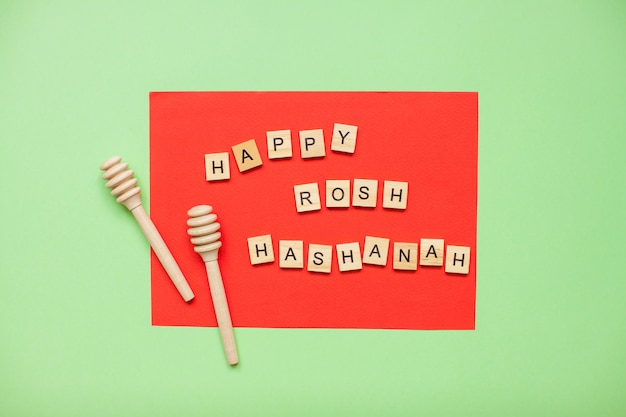 Слова из деревянных блоков 'happy rosh hashanah' и деревянные ложки для меда на красном и зеленом