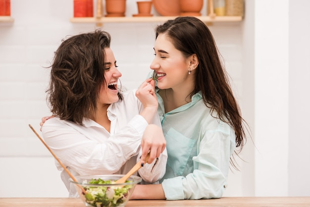 Happy same sex couple feed each other at kitchen