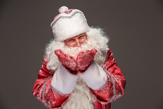 Happy santa claus in eyeglasses looking at camera on dark background