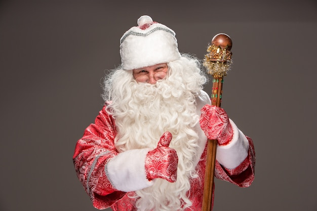 Happy santa claus in eyeglasses with staff on dark background