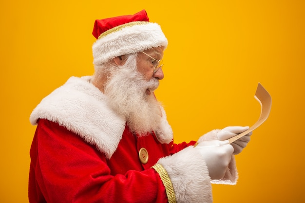 Happy santa claus holding vintage paper on yellow