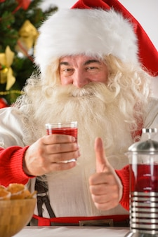 Happy santa claus at home eating cookies and drinking tea