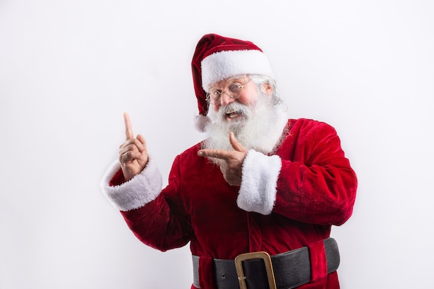 Happy santa claus, pointing a side in white wall
