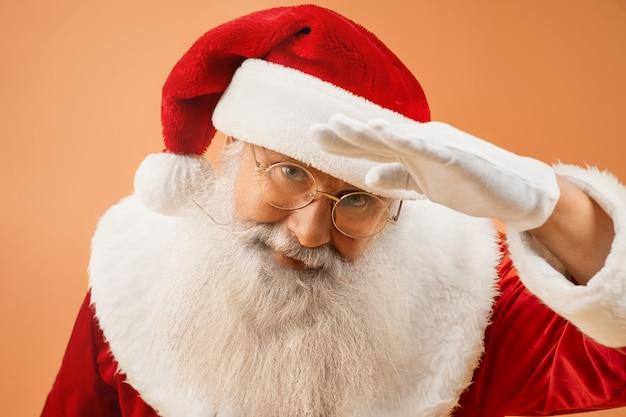 Happy santa claus posing in studio in traditional costume
