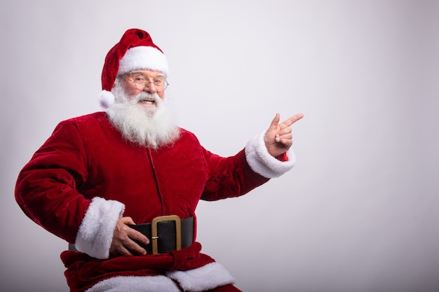 Happy santa claus, sat with hand in belt pointing a side in white wall