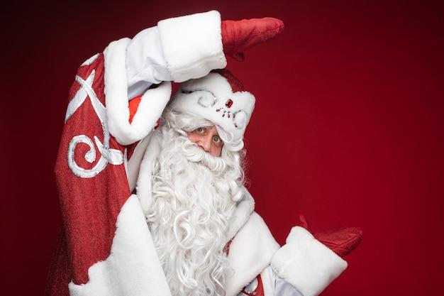 행복한 산타 클로스는 장갑에 손으로 크기 또는 치수를 보여줍니다.