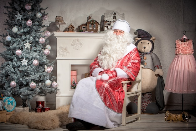 Happy santa claus sitting on on the of christmas decorations