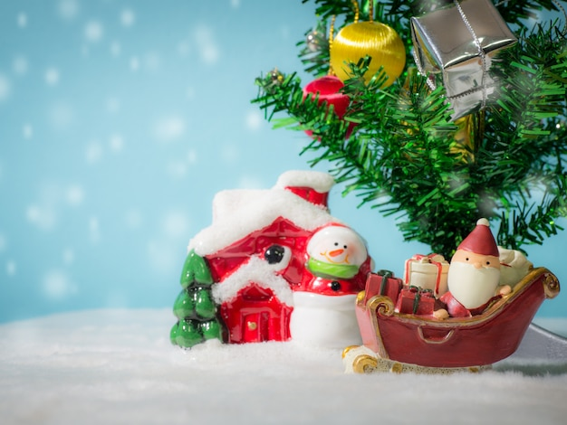Happy santa claus with gifts box on the snow sled going to house. near house have snowman and christmas tree.