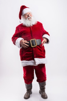 Happy santa claus, with hands in belt in white wall