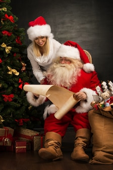 Happy santa claus with his woman helper near christmas tree