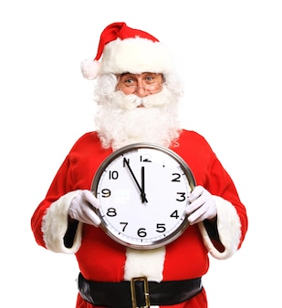 Happy santa in eyeglasses pointing at clock showing five minutes to christmas