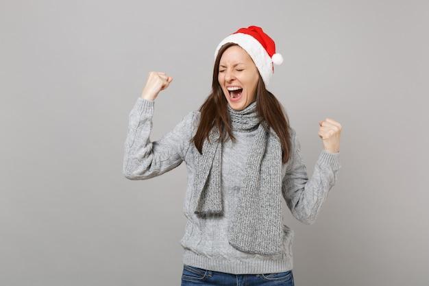 目を閉じて叫んで、灰色の背景に分離された勝者のジェスチャーをしているセータースカーフクリスマス帽子の幸せなサンタの女の子。明けましておめでとうございます2019お祝いホリデーパーティーのコンセプト。コピースペースをモックアップします。