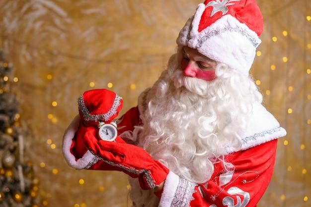 해피 산타는 크리스마스 트리 배경에 알람 시계와 표지판을 들고 크리스마스를 기다리고 있습니다.