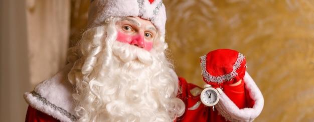 자정까지 5분 크리스마스 카드 선택적 초점을 보여주는 알람 시계가 있는 행복한 산타